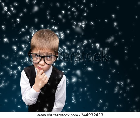 Cute boy in search of answers to questions.  - stock photo