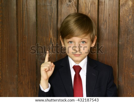 cute boy in suit and tie on a wooden background - stock photo
