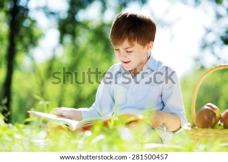 Cute boy in summer park sitting on blanket and reading book - stock photo