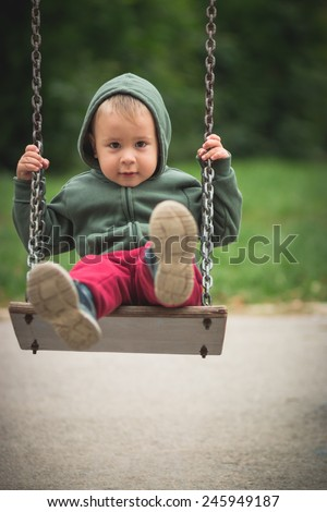 Cute boy in the hoodie swinging in the park - stock photo