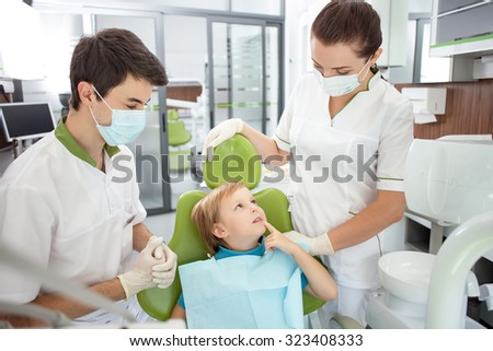 Cute boy is complaining of toothache. He is sitting in dental chair and pointing finger at tooth. He is looking at woman with hope. The dental doctor and assistant are listening to him attentively - stock photo
