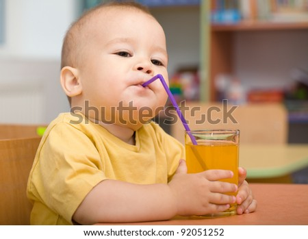 Cute boy is drinking orange juice using straw - stock photo
