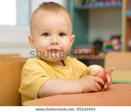 Cute boy is eating apple in preschool - stock photo