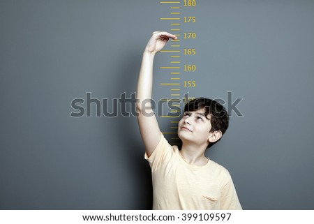 Cute boy is showing height on a wall scale. A cute boy is holding his arm up and showing his height on a wall scale. - stock photo