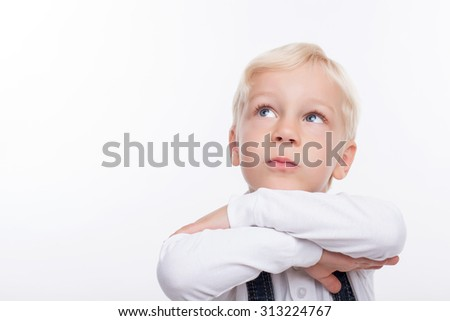 Cute boy is standing and dreaming. He crosses his hand and leaning his head on it. The boy is looking up pensively. Isolated and copy space in left side - stock photo