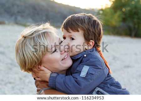 Cute boy kissing his mother - stock photo
