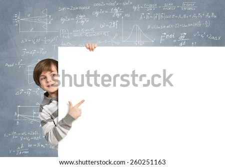 Cute boy looking from behind blank advertising board - stock photo