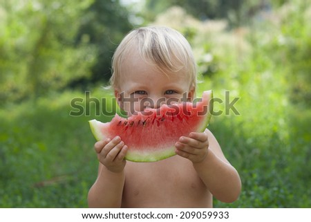 Cute boy looking to you and laughs, smiles. Blurred background - stock photo