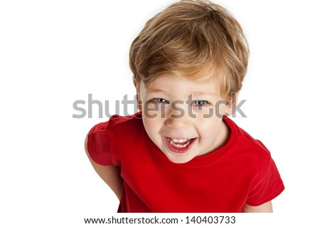 Cute boy looking up, smiling and laughing, wearing a red T-Shirt in a studio on a white background. - stock photo