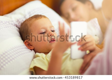 Cute boy lying on the bed and use the phone while mother sleeps, selective focus - stock photo