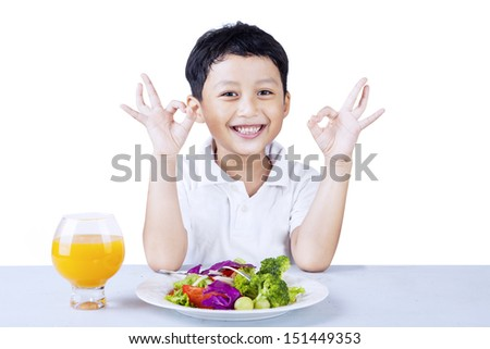 Cute boy making OK gesture while having salad, isolated on white - stock photo