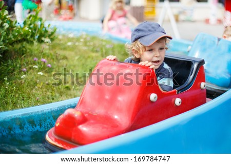 cute boy of two years having fun on water attraction in amusement park - stock photo