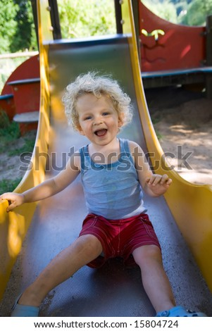 cute boy on a slide at the playground - stock photo