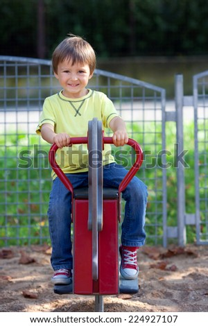 Cute boy on the playground, having fun, summertime - stock photo