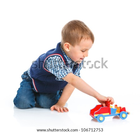 Cute boy plaing with toy car on floor, isolated on white - stock photo