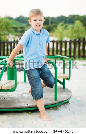 Cute boy playing at playground in a park - stock photo