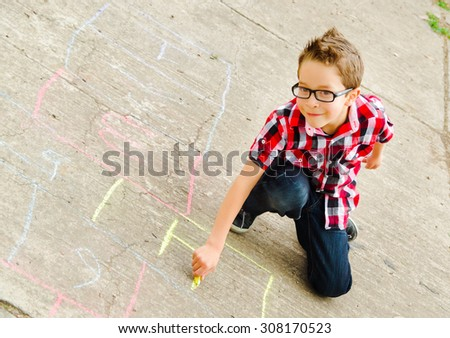 cute boy playing drawing hopscotch in the park - stock photo