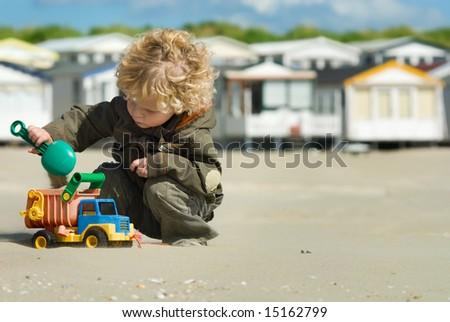 cute boy playing on the beach - stock photo