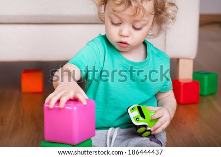 Cute boy playing with colorful block toys - stock photo