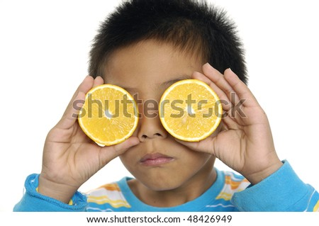 Cute boy playing with oranges a over white - stock photo