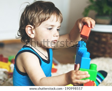 cute boy playing with toy blocks and bricks - stock photo