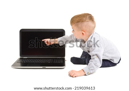 Cute boy points finger at the screen of laptop - stock photo