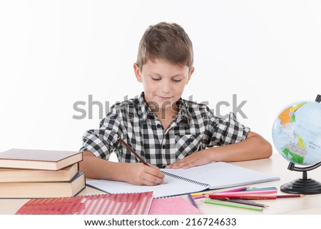 cute boy sitting at table and writing. handsome little schoolboy studying on white background - stock photo
