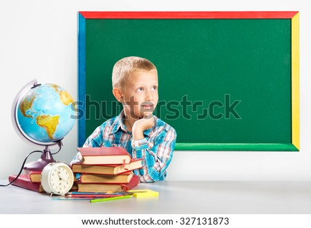 Cute boy sitting at the school table  - stock photo