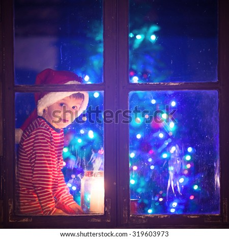 Cute boy, sitting on a window shield, playing on mobile phone at night, christmas time, waiting for Santa Claus, blue midnight filter applied - stock photo