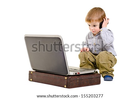 Cute boy speaks on a mobile phone looking at laptop - stock photo