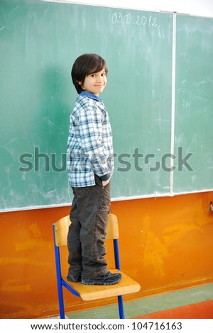 Cute boy standing on a chair in front of blackboard - stock photo