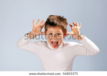 cute boy sticking his tongue out - stock photo