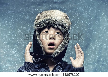 Cute boy surprised by snowfall - stock photo