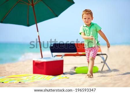 cute boy walking the sea beach - stock photo