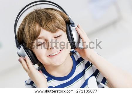 Cute boy wearing headphones and enjoying music - stock photo