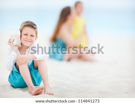 Cute boy with seashell at the beach with his family on background - stock photo