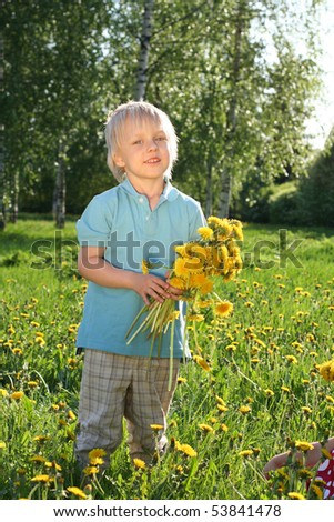 Cute boy with sunflowers in field - stock photo