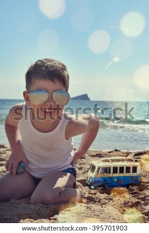 Cute boy with sunglasses on the beach - stock photo