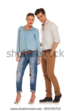 cute boyfriend and girlfriend posing in white isolated studio background looking at the camera. the man has one hand in pocket - stock photo