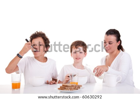 cute boys and mother taking breakfast, isolated on white, studio shot - stock photo