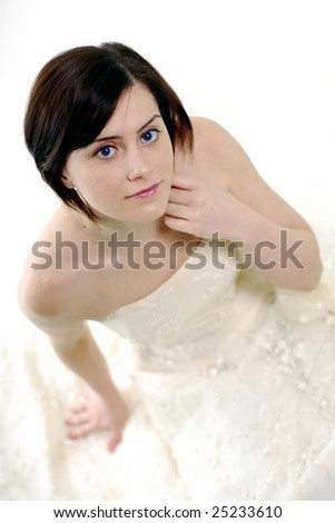 Cute bride looking upwards to the camera in a high key light - stock photo