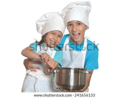Cute brother and sister posing in chef uniforms - stock photo