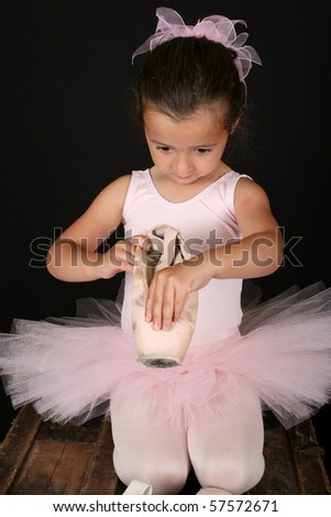Cute brunette ballet girl looking into a pointe shoe - stock photo