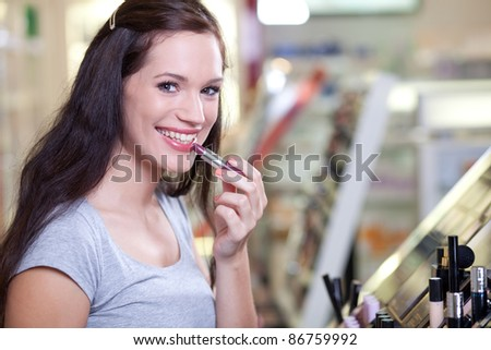 Cute brunette buying cosmetics. Applying lipstick in a drugstore. Shallow DOF. - stock photo