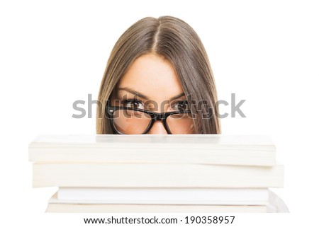 Cute brunette Caucasian student girl with glasses hiding behind books isolated on white background. Education concept. - stock photo