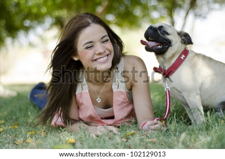Cute brunette girl having fun with her dog at the park - stock photo