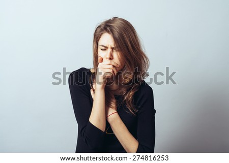 cute brunette girl in a fist coughs - stock photo