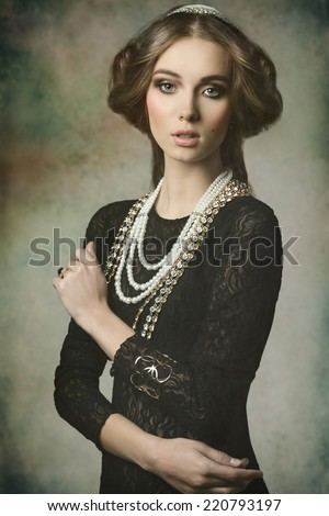 cute brunette girl posing in fantasy portrait wearing like a antique aristocratic lady with precious brilliant crown, vintage hair-style and brilliant jewellery   - stock photo
