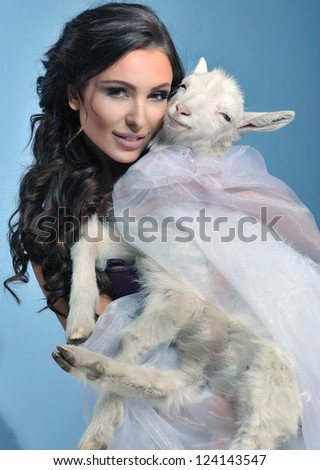 Cute brunette holding a little goat - stock photo