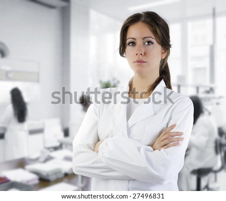 cute brunette in white medical gown in a research medical laboratory - stock photo